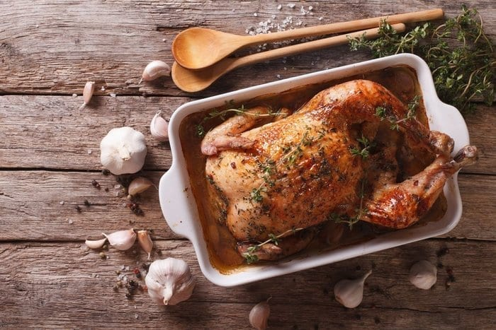 photo-of-roasted-chicken-in-a-pan-on-a-rustic-wood-table