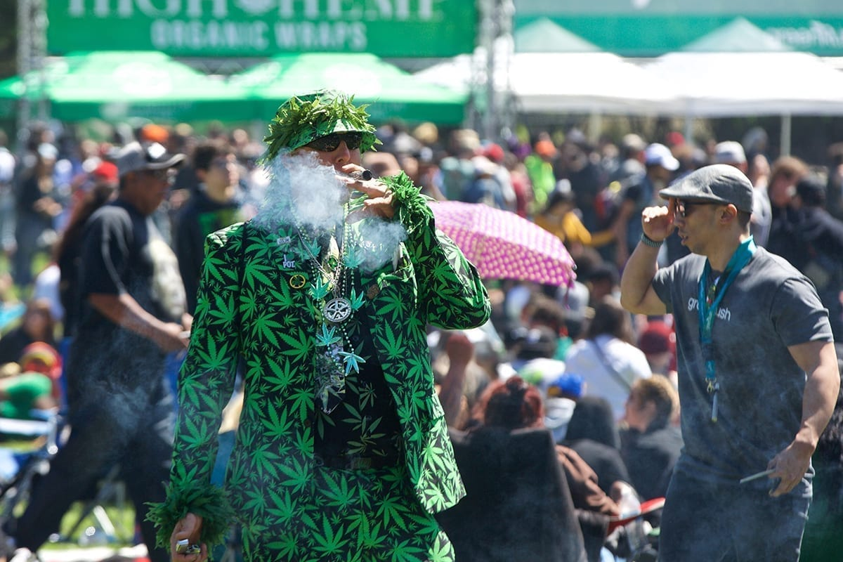 Mike Barnes of Hayward smokes while dressed in a marijuana leaf suit during the 420 event at Hippie Hill in Golden Gate Park on Friday, April 20, 2018. (Kevin N. Hume/S.F. Examiner)